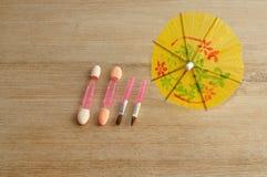 En uppsättning av små sminkborstar som visas med ett gult paraply Royaltyfri Fotografi