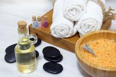 En uppsättning av Spa tillvägagångssätt från aromatiska oljor, mjuka handdukar, varma stenar och salt för bad i en träbunke med e Royaltyfri Bild