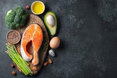 En uppsättning av sund mat för keto bantar på en mörk bakgrund Ny rå laxbiff med linfrö, broccoli, avokado, fega ägg arkivbild
