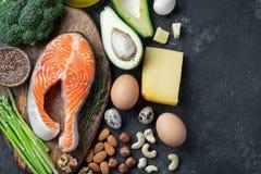 En uppsättning av sund mat för keto bantar på en mörk bakgrund Ny rå laxbiff med linfrö, broccoli, avokado, fega ägg royaltyfri bild