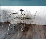 En uppsättning av tabell och stolar för att ha te eller frukosten att dekoreras i vita färger arkivfoto