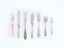 En uppsättning av tappning som äter middag knivar och gafflar av olika former och Royaltyfria Bilder
