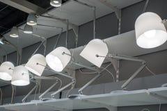 En uppsättning av vita skrivbordlampor på hyllor Royaltyfri Foto