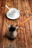 En uppsättning för turkiskt kaffe med Cezve på trätabellen Arkivbilder