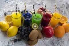 en upps?ttning av kalla nya sammanpressade fruktsafter eller coctailar i exponeringsglas som g?ras fr?n apelsinen, kiwi, citron,  arkivfoton