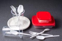 En upps?ttning av plast- redskap Plast- koppar, plattor, gafflar, skedar och plast- beh?llare p? en gr? bakgrund Mot plast- fotografering för bildbyråer
