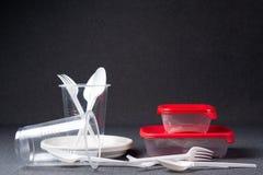 En upps?ttning av plast- redskap Plast- koppar, plattor, gafflar, skedar och plast- beh?llare p? en gr? bakgrund Mot plast- royaltyfri bild
