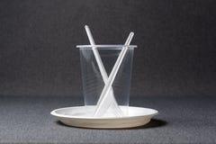En upps?ttning av plast- redskap Plast- koppar, plattor, gafflar, skedar och plast- beh?llare p? en gr? bakgrund Mot plast- arkivfoton