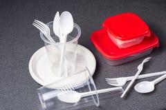 En upps?ttning av plast- redskap Plast- koppar, plattor, gafflar, skedar och plast- beh?llare p? en gr? bakgrund Mot plast- arkivfoto