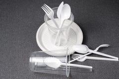 En upps?ttning av plast- redskap Plast- koppar, plattor, gafflar, skedar och plast- beh?llare p? en gr? bakgrund Mot plast- arkivbild