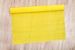 En uppvecklad rulle av gult korrugerat papper ligger på golv royaltyfri foto