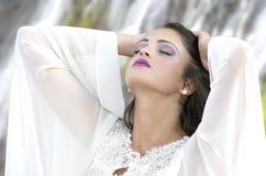 En ursnygg ung kvinna som framme står av en rusavattenfall Royaltyfri Foto