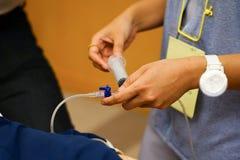 En utbildningssjuksköterska som injicerar läkarbehandlingen under CPR-utbildningskurs arkivfoton