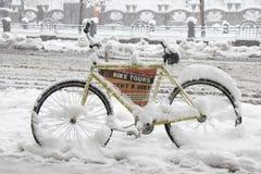 En uthyrnings- cykel som parkeras på trottoaren i tungt snöfall arkivfoton
