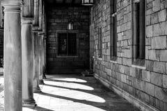 En utomhus- borggårdkorridor i svartvitt med pelare och sten och fönster Arkivbild