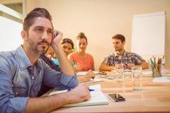 En uttråkad formgivare under ett möte royaltyfri bild