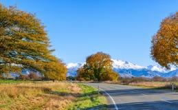 En väg med en härlig sikt nära snö-korkade berg på den soliga höstmorgonen, Canterbury, södra ö, Nya Zeeland arkivfoto