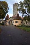 En väg som leder till stadporten i en gammal byggnad med stenbågen i Rothenburg obder Tauber arkivbilder