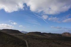 En väg som spolar dess väg till och med det vulkaniska landskapet av timanfayanationalparken lanzarote Arkivfoto