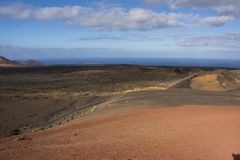 En väg som spolar dess väg till och med det vulkaniska landskapet av timanfayanationalparken lanzarote Arkivbild