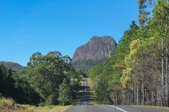 En väg till och med exponeringsglasbergen av Queensland Australien som blickar som den är den hövdade raksträckan in mot ett hägr arkivbild