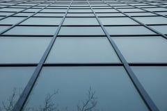 En vägg av en byggnad av blåa exponeringsglasfyrkantfönster Fotografering för Bildbyråer