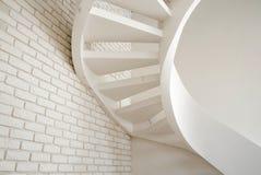 En vägg av vit tegelsten och en spiraltrappuppgång i huset royaltyfri foto