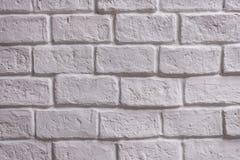 En vägg av vit tegelsten som åldras vid tid och bleknar av wheather Ett stenarbete och bakgrund för hus planlägger Arkivfoton