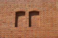 En vägg för röd tegelsten, två bricked-upfönster arkivfoto