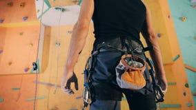 En vägg i en bouldering idrottshall och en man med speciala inventariet som det är klart att klättra det stock video