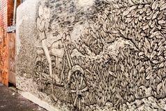 En vägg som vandaliseras med gatagrafittikonst Arkivbilder