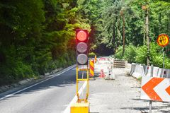 En vägtrafikrörelse på vägen under reparationsarbete med röd trafikljus Skadad väg i underhåll fotografering för bildbyråer
