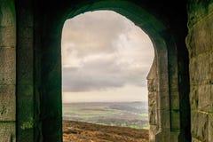 En välvd dörröppning som ut ser på hederna på en stormig dag royaltyfri bild