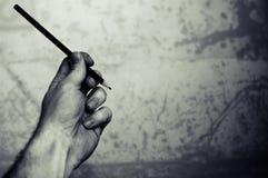 En vänstersidahand med en blyertspenna Arkivfoton