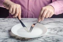 En väntande på mat för unidentifiable man arkivfoto