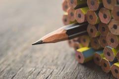 En vässad blyertspenna som står ut från den annan nya blyertspennan på w Fotografering för Bildbyråer