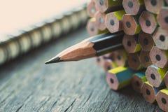 En vässad blyertspenna som står ut från den annan nya blyertspennan på w Arkivbild