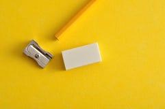 En vässare, ett radergummi och en gul blyertspenna royaltyfri bild