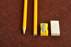 En vässare, ett radergummi och en gul blyertspenna två Royaltyfri Bild