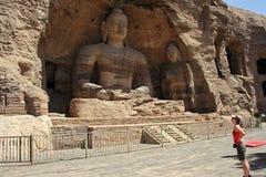 En västra turist ser den stora Buddha av Yungangen Grott Royaltyfri Bild
