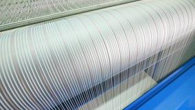 En vävstol rullar vita trådar som arbetar på en textilfabrik arkivfilmer