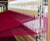 En vävstolaktivering med röd ull snedvrider trådar som är klara för att väva Arkivbild