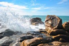 En våg av vatten som förnyar en sten royaltyfria bilder