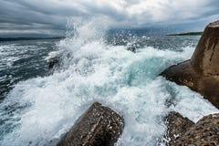 En våg, ett havsskum och en vågbrytare Arkivbild