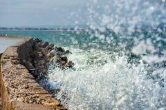 En våg, ett havsskum och en vågbrytare Royaltyfria Bilder