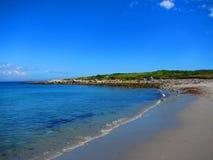 En våg tvättar sig onshore på en strand Arkivbilder