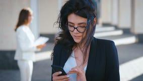 En vacker ung affärskvinna med smartphone-sms-budbärare och leende utanför samtidigt som hon arbetar på arkivfilmer