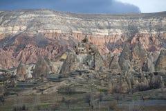 En vagga med boningar av forntida kristen på en dyster Januari dag Cappadocia Turkiet royaltyfri fotografi
