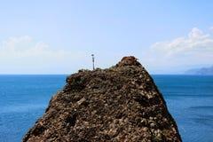 En vaggatextur av ett bergigt vaggar på vilket en torkad ensam växt mot det blåa havet och himlen Maximumet av berget ovanför hav royaltyfri bild