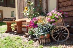 en vagn med blommor och en bänkingång till huset Royaltyfri Bild